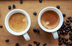 Two espresso coffees in small white cups,with a coffee bean rest Stock Photos