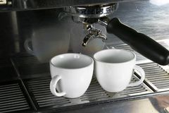 Two Espresso Cups. Two white cups waiting under an espresso machine ready Royalty Free Stock Images