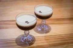 Two espresso martini cocktail drinks with coffee beans on top royalty free stock photography