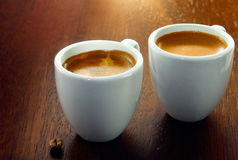 Two espressos with a single coffee bean. Two espresso coffees in small white cups,with a single coffee bean resting on the wood background Stock Images