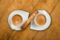 Espresso and Biscotti. Two Espressos in unique white cup and saucer with Biscotti in the center all on wooden background stock image