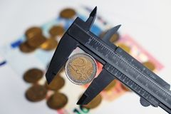 Two Euro coin being hold by a vernier tool Royalty Free Stock Photography