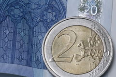Two Euro coin on a blue twenty euro bank note Royalty Free Stock Image