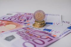 Two euro coin. Close up view, 500 Euro in background Stock Photos