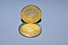 Two Euro coins heads. Two Euro coins made in Greece close up on grey surface stock images