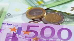 Two Euro coins over bank notes rotating. Two Euro coins over bank notes background rotating, loop ready stock footage