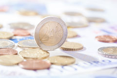 Two Euro standing on bank notes and coins Stock Photos
