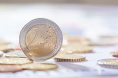 Two Euro standing on bank notes and coins Stock Images