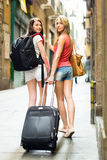 Two european girls on road to hotel on foot Stock Image
