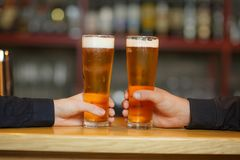 Two men cling to full glasses with a beer. Close-up. stock photos
