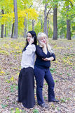Two European women talking by cellular in park Royalty Free Stock Photo