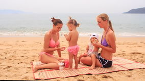Two european young mothers and little daughters sit on mat bite off rolls and drink beverages against bay and hills stock footage