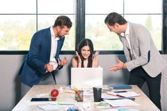 Two men viciously yells at the girl, the girl cries and hides her hands. Inside the office. Two evil men aggressively shout at the girl and expressively gesture Stock Photography