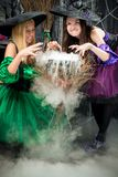 two evil witches brew a potion in the pot Stock Image