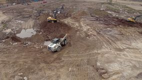 Two excavators load a dump truck aerial shot stock footage