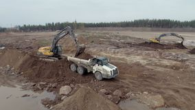 Two excavators load a dump truck stock video footage
