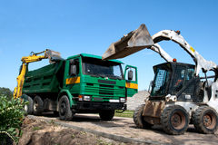 Two excavators loaded dumper. At construction site royalty free stock photography