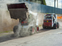 Two excavators perform milling of asphalt. And aspiration of debris Royalty Free Stock Images