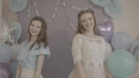 Two excited attractive young women in fancy pretty dresses with air balloons in hands turning around smiling in camera. Two excited attractiveyoung women in stock video footage