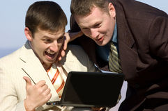 Two excited businessmen with laptop. Two excited European businessmen laugh watching laptop royalty free stock image
