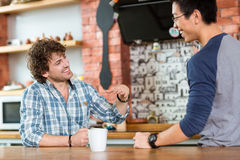 Two excited cheerful guys sitting, talking and laughing in cafe Royalty Free Stock Photography