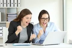 Two excited executives celebrating success. Reading good news in a laptop at office royalty free stock images
