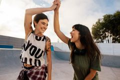Skaters high five at skate park. Two excited female friends high fiving at skate park. Beautiful women having a great time at skate park Royalty Free Stock Photos