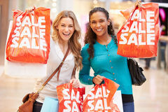 Two Excited Female Shoppers With Sale Bags In Mall. Looking At Camera Smiling Royalty Free Stock Image