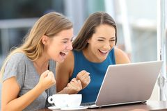 Excited friends finding on line content in a laptop. Two excited friends finding on line content in a laptop sitting in a restaurant terrace Stock Photos
