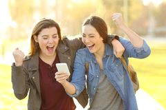 Excited friends watching phone content in a park stock images