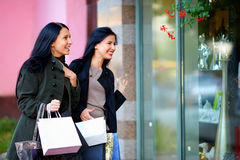 Two excited happy women looking in shop window Stock Photography