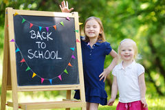 Two excited little sisters by a chalkboard Royalty Free Stock Photo