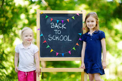 Two excited little sisters by a chalkboard Stock Photo