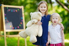 Two excited little sisters by a chalkboard Stock Images