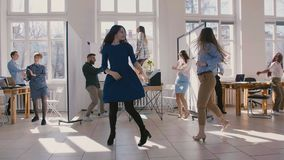 Two excited office manager women doing crazy fun victory dance together with happy multiethnic colleagues slow motion. Cheerful happy business people celebrate stock video footage