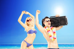 Two excited people dancing on a music on a beach Stock Photos
