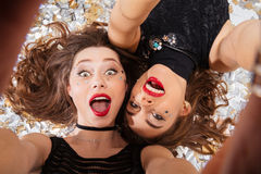 Two excited pretty women taking selfie and lying. Two excited pretty young women with red lips taking selfie and lying on background of shining confetti Royalty Free Stock Photos