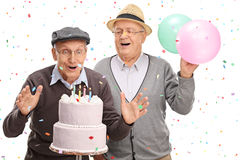 Two excited seniors blowing candles on a cake Stock Images