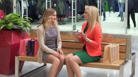 Two excited shopping woman resting on bench at shopping mall stock video footage