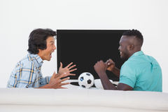 Two excited soccer fans watching tv. Side view of two excited soccer fans watching tv Stock Photo