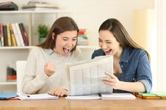 Two excited students reading a newspaper. Two excited students reading good news in a newspaper at home Stock Images