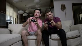 Two excited teen friends having fun playing TV games with wireless joysticks at home in slow motion -. Two excited teen friends having fun playing TV games with stock video footage