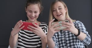 Excited teenage girls playing game on mobile phones stock footage