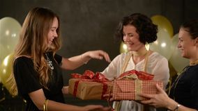 Two Excited Women Congratulate Their Friend Hugging Her and Giving a Presents. Birthday Girl Recieved Boxes with Gifts. Black Background with White and Golden stock footage