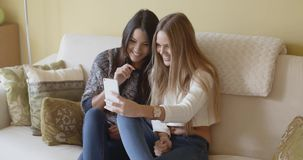 Two excited young woman reading an sms. Or text message on a mobile phone as they sit together relaxing on a sofa stock video