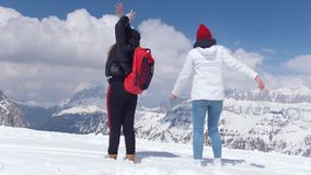 Two excited young women walking on the snow in Dolomites with big backpack and guitar and waving hands stock video footage