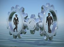 Two Executive managers walking inside gears at sea. Two executives walking inside gears at sea demonstrates their talent and effectiveness Royalty Free Stock Photography