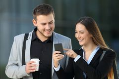 Two executives talking about phone content. Front view of two happy executives talking about smart phone content standing outdoors on the street royalty free stock images