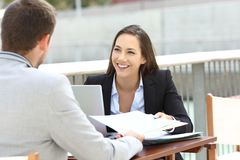 Two executives working sharing informs. Sitting in a bar terrace royalty free stock photo