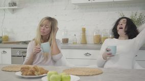 Two exhausted adult Caucasian women sitting at the table in the morning with coffee cups and yawning. Portrait of tired
